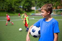 Enfants jouant le football dans un stade Photographie stock