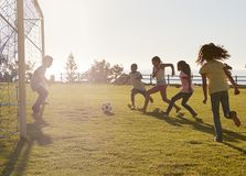 Enfants jouant le football en parc, un dans le but, vue de côté Photos stock