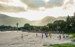 Enfants jouant le football sur la plage Images libres de droits
