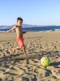 Enfants jouant le football sur la plage Image libre de droits