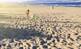 Enfants jouant le football sur la plage Photos stock