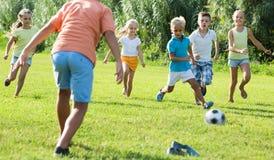 Enfants jouant le football sur le pré Photo libre de droits
