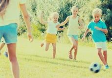 Enfants jouant le football sur le pré Photos stock