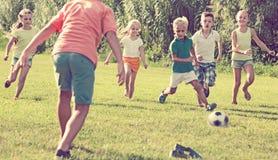 Enfants jouant le football sur le pré Photographie stock