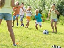 Enfants jouant le football sur le pré Photos libres de droits