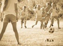 Enfants jouant le football sur le pré Photo stock
