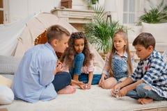 Enfants jouant le jeu de domino ensemble à la maison Photos libres de droits