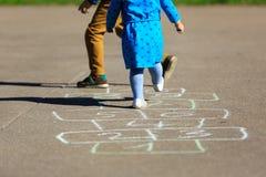 Enfants jouant le jeu de marelle sur le terrain de jeu dehors Photo stock