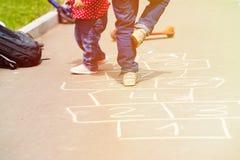 Enfants jouant le jeu de marelle sur le terrain de jeu dehors Photographie stock