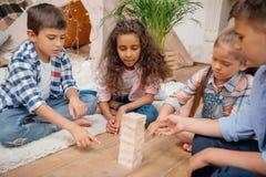 Enfants jouant le jeu en bois de blocs ensemble à la maison Photo libre de droits