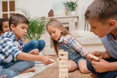 Enfants jouant le jeu en bois de blocs ensemble à la maison Image libre de droits