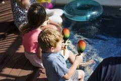 Enfants jouant par une piscine images stock
