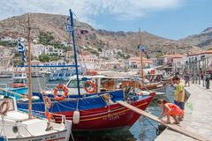 Enfants jouant près d'un bateau de pêche à l'hydre grecque d'île Images stock
