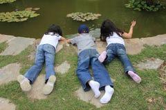 Enfants jouant près de l'étang dans un jardin image stock