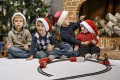 Enfants jouant près de l'arbre de Noël avec des cadeaux Image stock