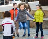 Enfants jouant sauter d'une bande élastique Image stock