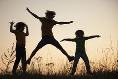 Enfants jouant sauter sur le pré de coucher du soleil d'été silhouetté images stock