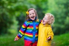 Enfants jouant sous la pluie Photographie stock