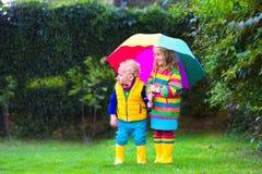 Enfants jouant sous la pluie sous le parapluie coloré Photo libre de droits