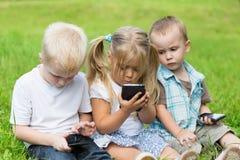 Enfants jouant sur des smartphones se reposant sur l'herbe Photos libres de droits