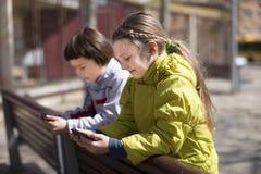 Enfants jouant sur des smartphones sur le banc de rue Images libres de droits