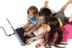 Enfants jouant sur l'ordinateur portatif image libre de droits