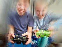 Enfants jouant sur la console de jeux Images libres de droits