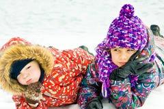 Enfants jouant sur la neige dans l'horaire d'hiver Images libres de droits