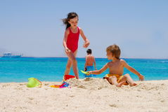Enfants jouant sur la plage Photos libres de droits