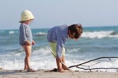 Enfants jouant sur la plage de sable Photos libres de droits
