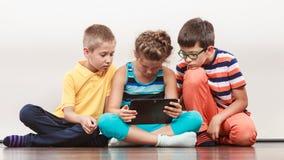 Enfants jouant sur la tablette Photo stock