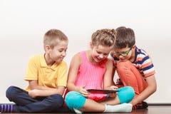 Enfants jouant sur le comprimé photo stock