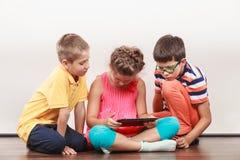 Enfants jouant sur le comprimé image stock