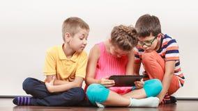 Enfants jouant sur le comprimé photos stock