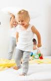 Enfants jouant sur le grand lit Photos libres de droits