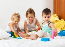 Enfants jouant sur le lit Photographie stock