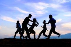 Enfants jouant sur le pré de coucher du soleil d'été Image stock