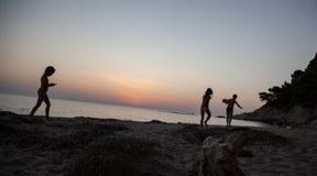 Enfants jouant sur le pré de coucher du soleil d'été, jouer heureux d'enfants Images libres de droits