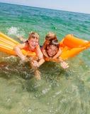 Enfants jouant sur un matelas gonflable Photographie stock