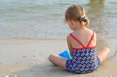 Enfants jouant sur une plage sablonneuse et une eau salée Photographie stock