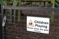 Enfants jouant svp le signe étroit de porte au parc de terrain de jeu dehors Photo stock
