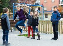 Enfants jouant une bande élastique Photos libres de droits