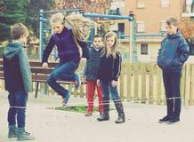 Enfants jouant une bande élastique Images libres de droits