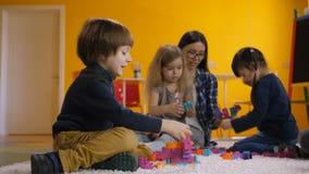 Enfants joyeux appréciant des loisirs dans le jardin d'enfants banque de vidéos