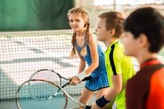 Enfants joyeux ayant l'amusement sur le court de tennis Photographie stock