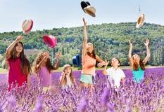 Enfants joyeux jetant en l'air vers le haut des chapeaux dans le domaine de lavande Photographie stock