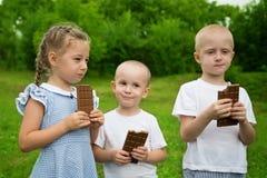 Enfants joyeux mangeant du chocolat dehors Photo stock