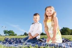 Enfants joyeux s'asseyant sur la couverture Images stock
