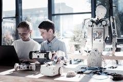 Enfants joyeux travaillant dans l'atelier et des machines robotiques de programmation Photos libres de droits