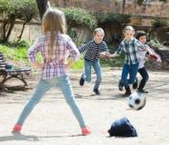 Enfants juniors jouant le football de rue dehors Photographie stock